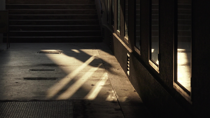Shadowplay and reflections : passerbys walking through a passage (gangway)