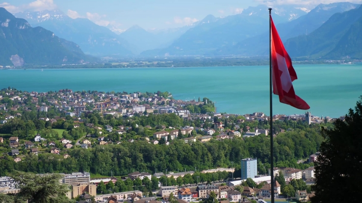 View across Lake Geneva at Lausanne with Swiss flag flying in the wind.