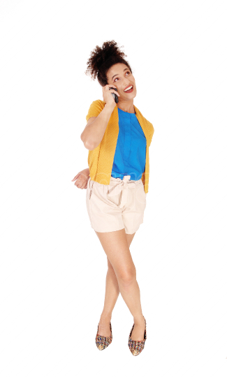 A beautiful woman standing in shorts talking at her cell phone