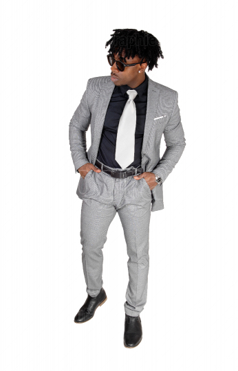 A black young man standing in a gray suit and sunglasses