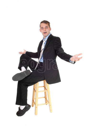 A business man sitting on a chair is perplex