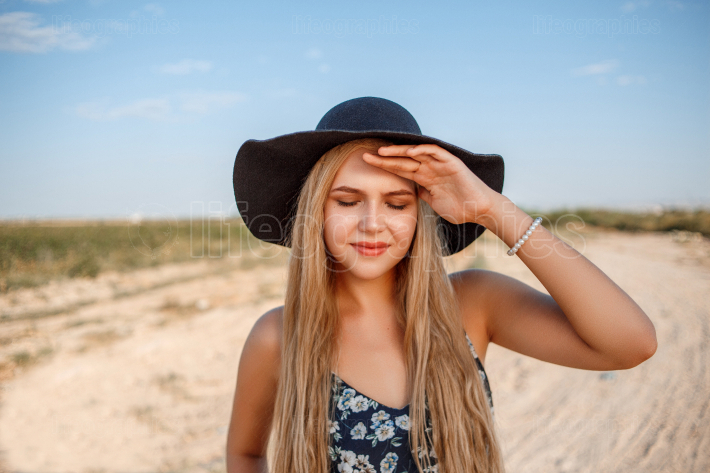A close up portrait of a blue eyed blonde girl in a black hat an