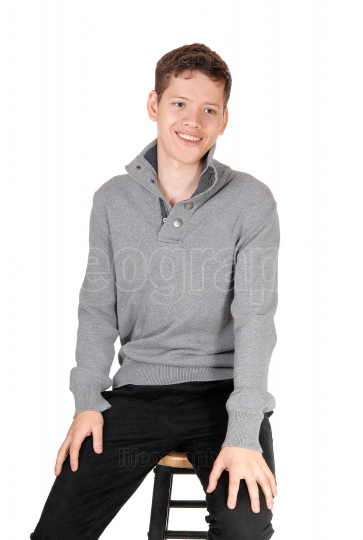 A happy smiling and relaxed teen boy sitting on a chair