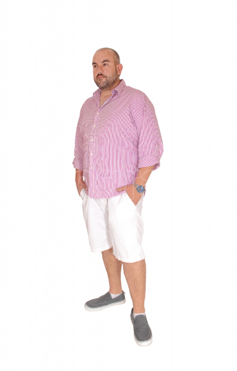 A Hispanic man standing in the studio relaxing