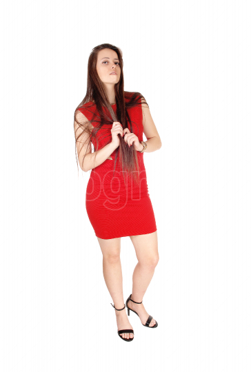 A lovely young woman standing in profile in a red dress