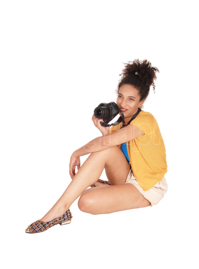 A multi racial woman sitting on the floor with her camera