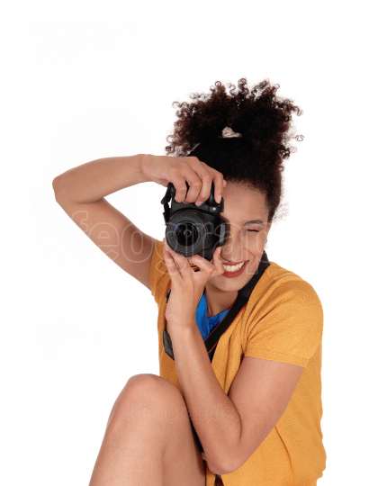 A multi racial woman taking pictures in the studio