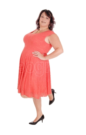 A plus size woman standing in a red dress