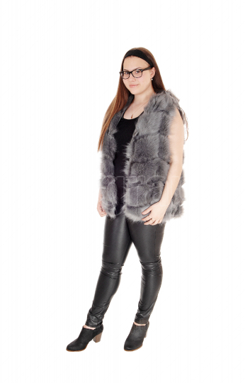 A pretty teenager girl standing in leather pants and fur jacket