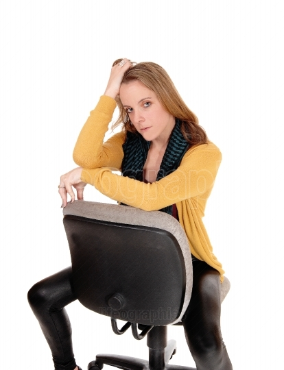 A serious looking woman sitting backwards on office chair