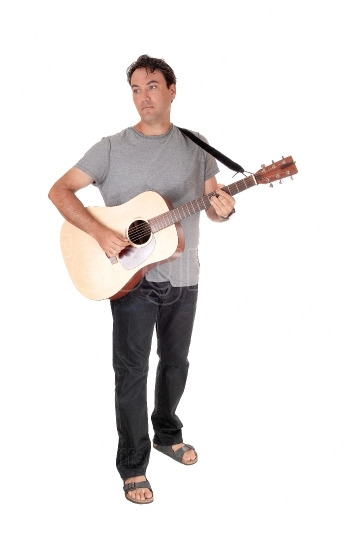 A tall man standing playing his guitar