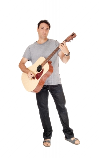 A tall man standing with his guitar and playing