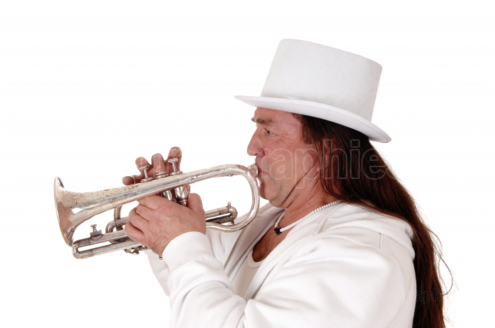 A trumpet player standing in a white outfit and cylinder in clos