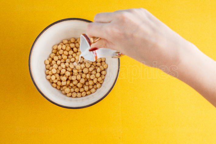 A woman s hand pours milk into honey balls from different cereal