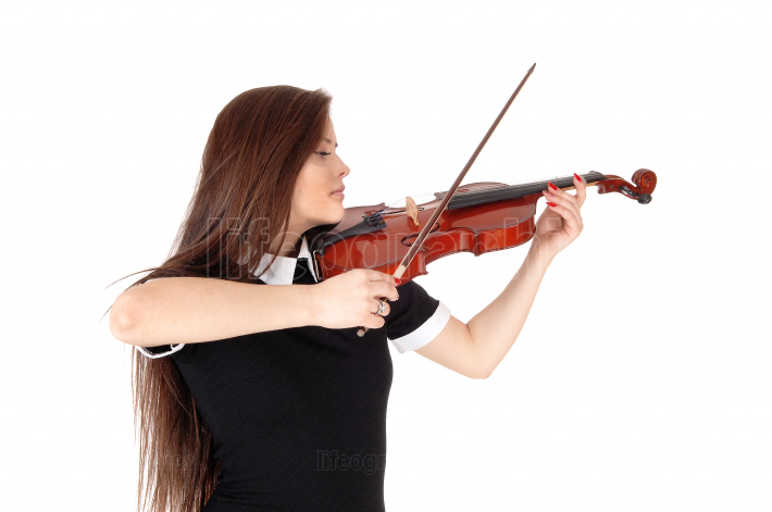 A woman standing in close up, playing the violin