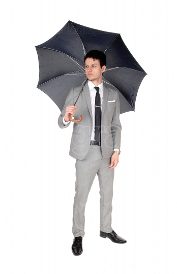 A young  man standing with an open umbrella