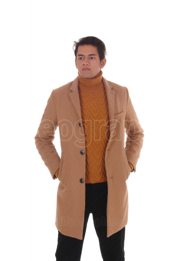 A young handsome man standing in a beige coat
