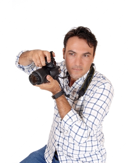 A young man holding his camera ready for a shoot