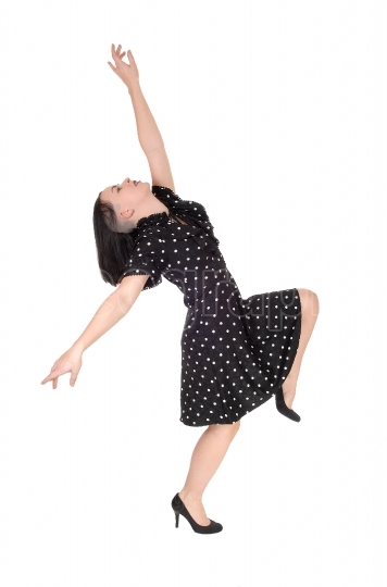 A young woman dancing in a pock dot dress