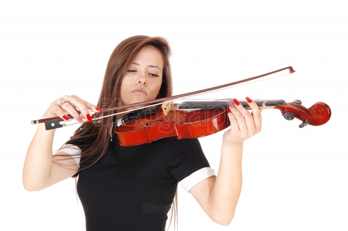 A young woman standing in close up playing the violin