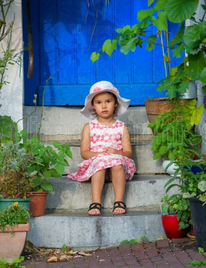 Adorable little girl wearing white hat  sitting on stairs on warm and sunny summer day