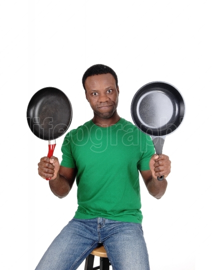 African American man holding up two freeing pan