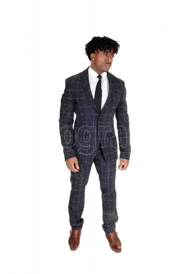 African man in a dark suit standing in the studio with fussy bla