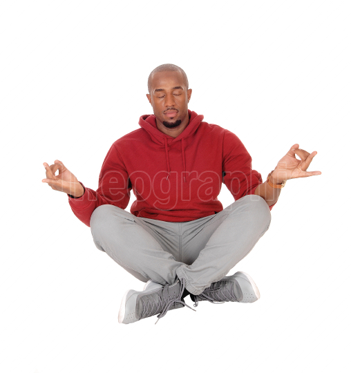 African man sitting on floor in a yoga pose