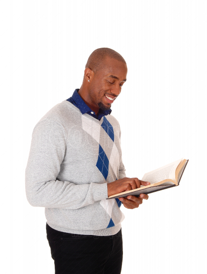 African man standing, reading a book