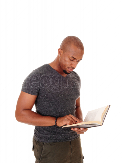 African man standing, reading in his book
