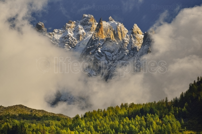 Aiguilles mountain peaks through clouds and blue sky. Chamonix, France