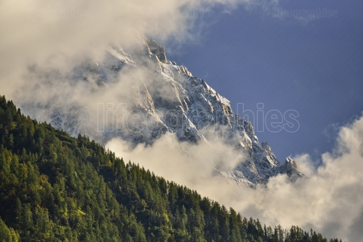 Aiguilles mountain range peaks and green forest through the clouds. Chamonix, France