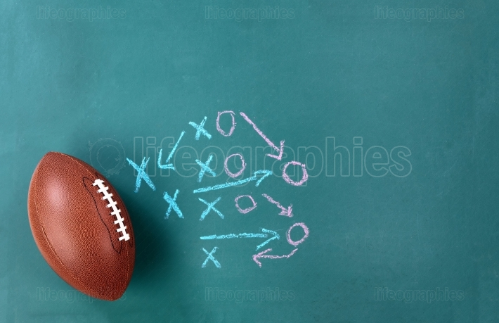 American Football with game plan on green chalkboard