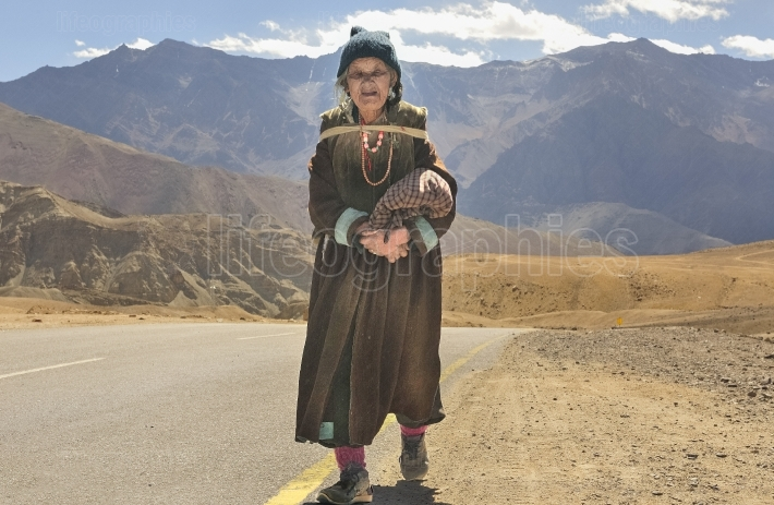 An old ladakhi woman walk along a paved road to Leh town