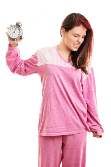 Angry girl in pajamas throwing an alarm clock