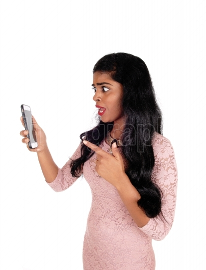 Angry woman looking at phone.