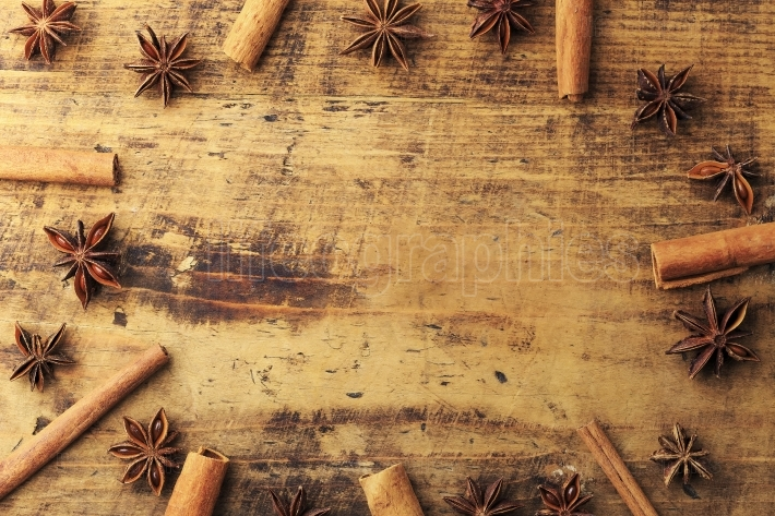 Anise star and cinnamon sticks over wood background