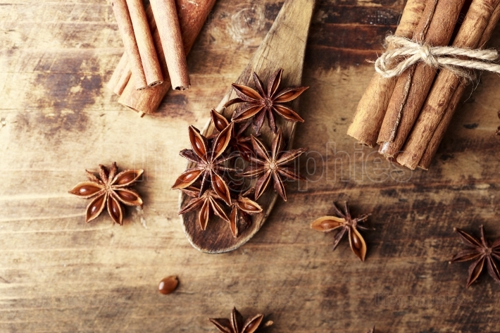 Anise star cinnamon sticks over wood background