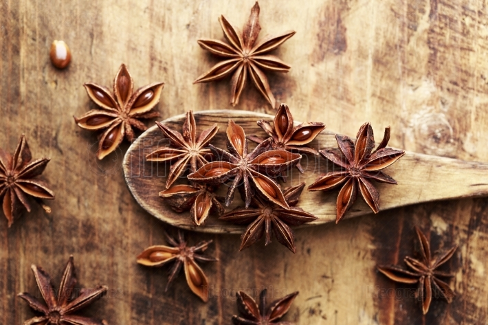 Anise stars on wood spoon close up