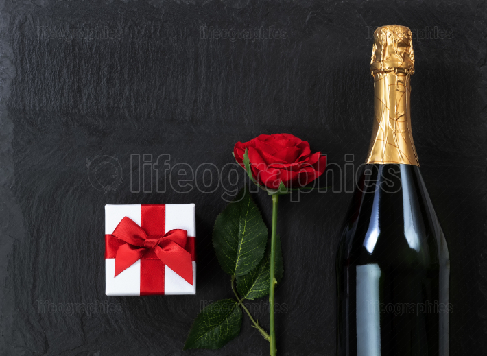 Anniversary background with champagne and gifts on natural slate