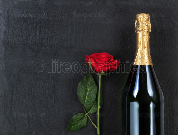 Anniversary background with single red rose and champagne on nat