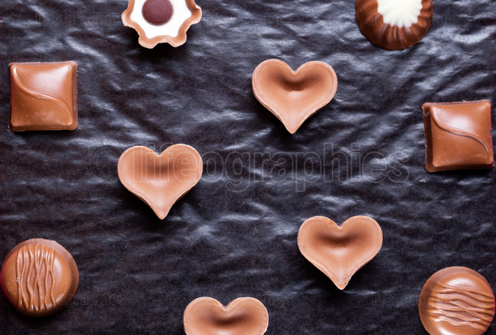 Assortment of chocolate candies over black background
