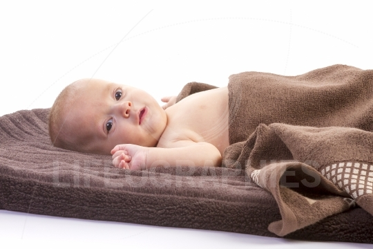 Baby boy over brown blanket