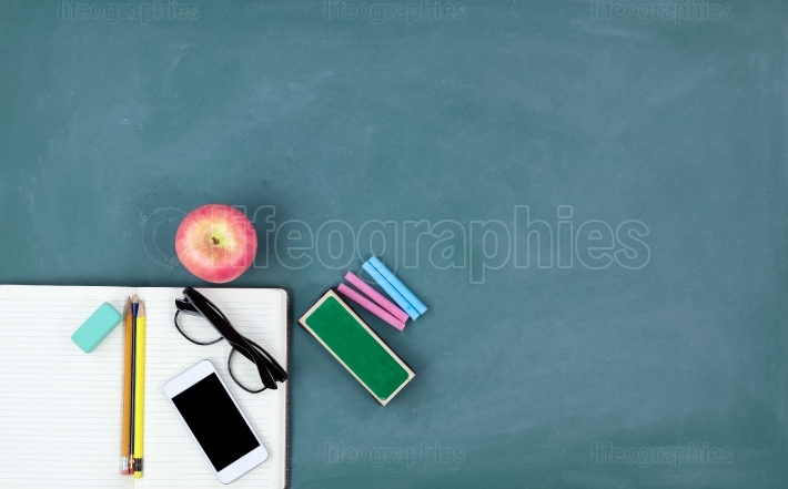 Back to school concept with basic stationery on a green chalkboa
