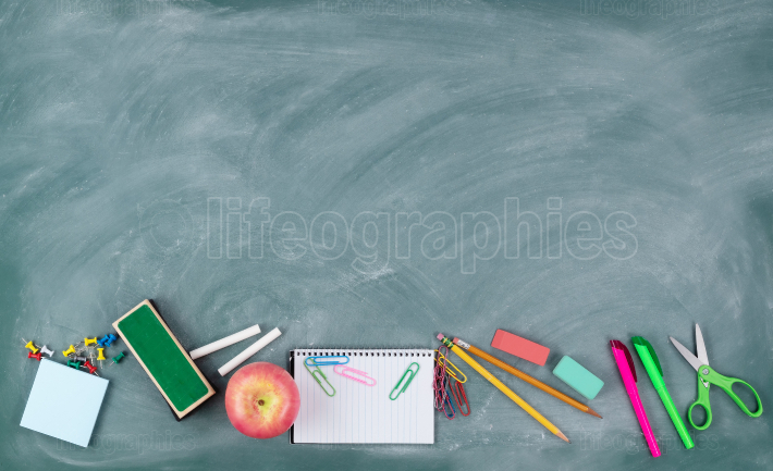 Back to school concept with erased green chalkboard and student
