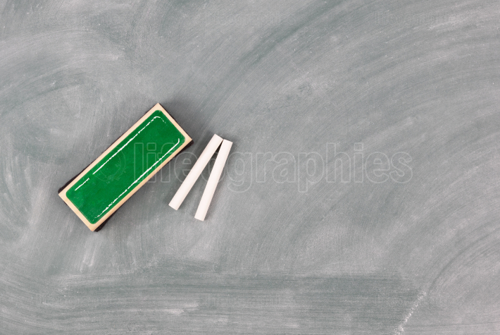 Back to school concept with green chalkboard plus eraser and cha