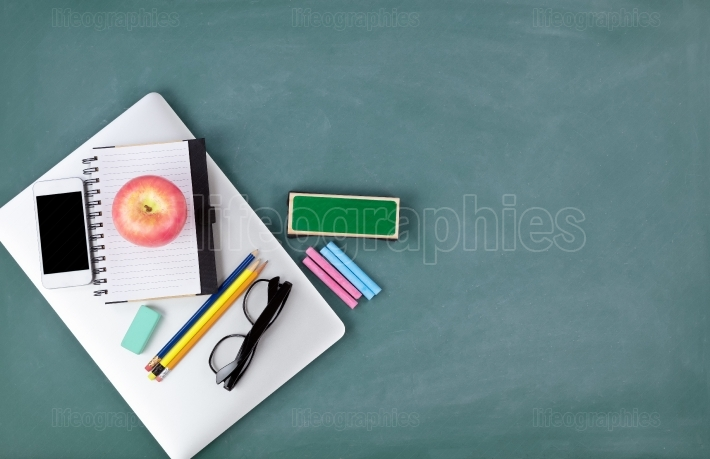 Back to school concept with technology and stationery on a green