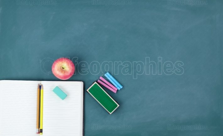 Back to school concept with writing stationery on a green chalkb