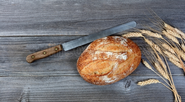 Baked whole wheat loaf of bread with cutting knife and stalks on