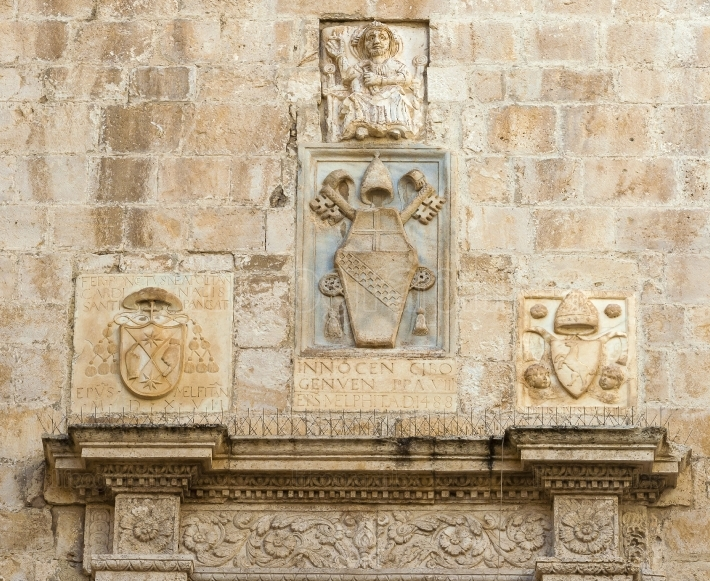 Bas reliefs of stone with Latin inscription surmounting the entrance of the cathedral bisceglie, Puglia  Italy